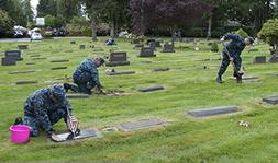 U.S. Sailors maintain gravesites at a cemetery during a CPO